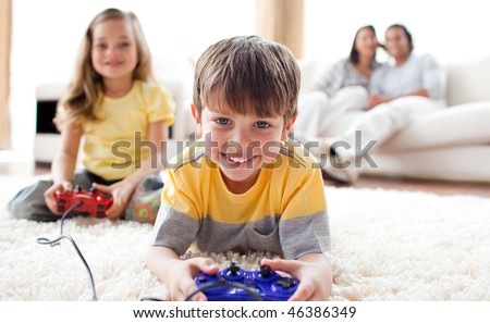 Cute little boy playing video game with his sister lying on the floor