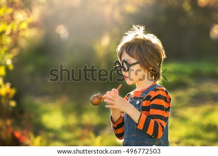 Cute little boy, playing with halloween costume in the park on sunset
