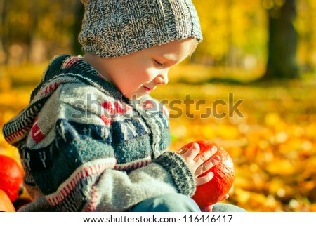 cute little boy playing with pumpkin in the park