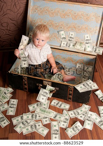 Cute little boy sitting in a suitcase with the money