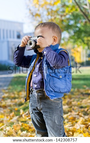 Cute little boy standing outdoors photographing with a retro camera held to his eye