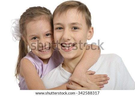 Cute little brother and sister hugging on white background