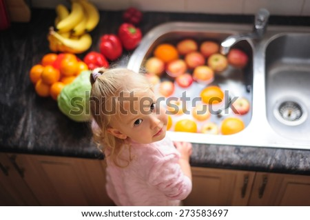 Cute little child, a toddler girl with blonde curly hair helping by washing healthy fruit and vegetables in a sink indoors in a kitchen