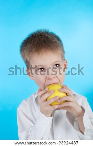 cute little child eating the apple on the blue background
