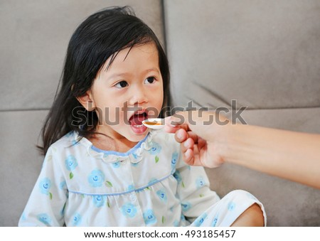 Cute little Child girl receiving pill at home