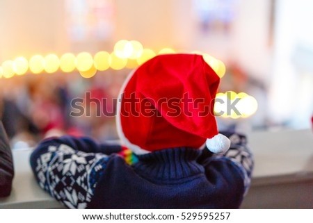 Cute little child on Christmas in a church. Praying kid boy with lights on background. Celebration of Xmas eve, big christian, catholic holiday