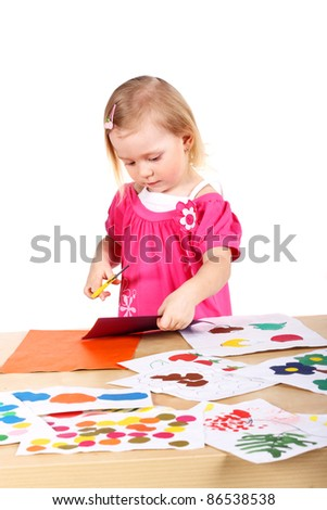 cute little child with colored paper in studio