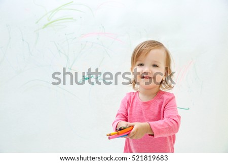Cute little girl drawing on light wall