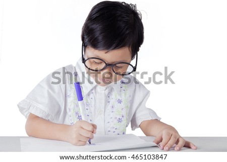 Cute little girl drawing on the paper using a marker, isolated on white background