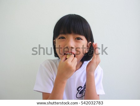 Cute little girl eating candy
