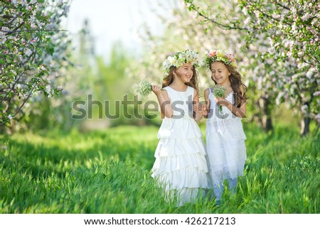 Cute little girl holding a flower outdoors in a green park