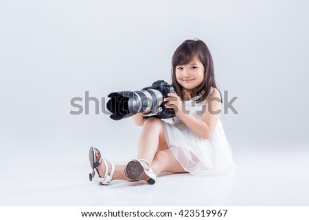 cute little girl in a white dress holding a big digital camera. child photographs