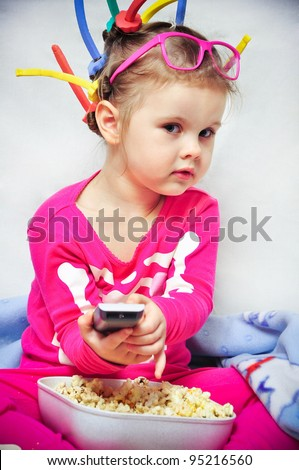 Cute little girl in curler eating popcorn and watching TV