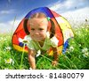 Cute little girl is playing outdoors under tent - stock photo