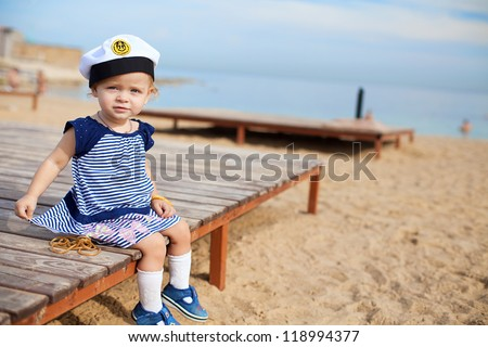 Cute little girl is 1 year old, posing on the beach by the sea on a background of blue sky, sitting.