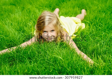 Cute little girl lies on a green lawn in summer day and smiling.
