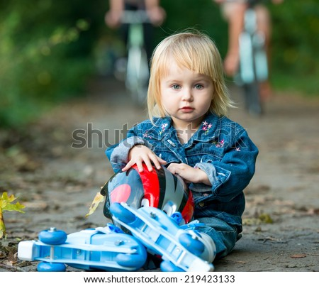Cute little girl on roller skates sitting on road in the park