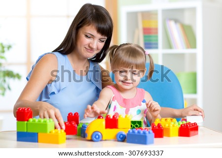 Cute little girl playing block toys with mother at home
