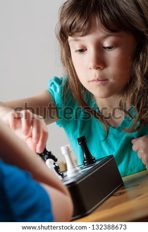 Cute little girl playing chess
