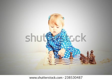 cute little girl playing chess indoors, early learning
