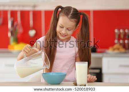 Cute little girl pouring fresh milk into bowl at kitchen