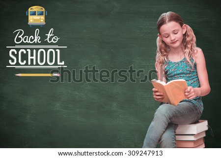 Cute little girl reading book in library against green chalkboard