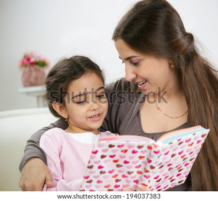 Cute little girl reading book with mother at home