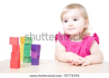 Cute little girl sitting at the table and playing with bricks