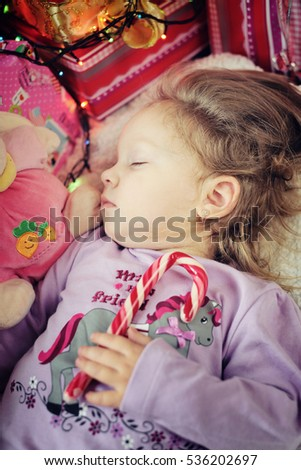 Cute little girl sleeping with Christmas candy cane