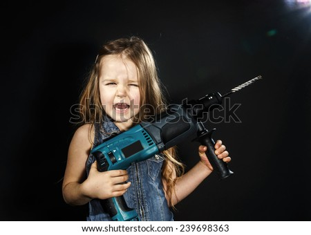 Cute little girl with drilling machine in her hands ready to professional constructing work