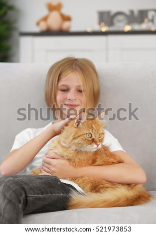Cute little girl with red fluffy cat on sofa in room