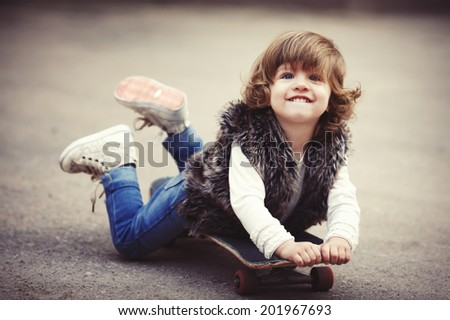 cute little hipster girl with skateboard portrait