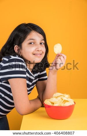 cute little indian girl eating chips or potato wafers, asian girl eating potato chips,  small girl eating chips in red bowl, over yellow background