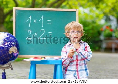 Cute little kid boy with glasses at blackboard practicing mathematics, outdoor. school or nursery. Back to school concept