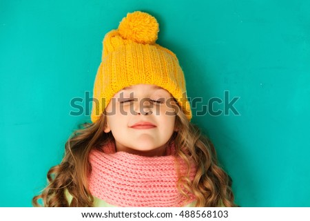 Cute little lady wearing yellow woolen cap and scarf imagine something
