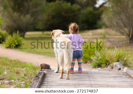 Cute little toddler girl playing with her dog labrador in a park on a warm summer day