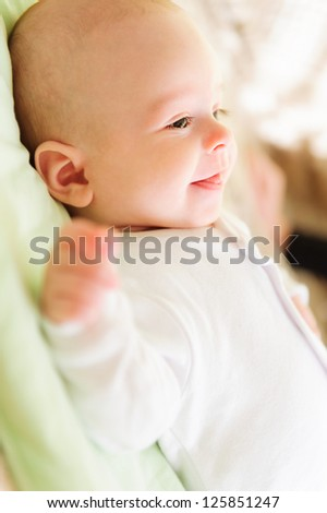 Cute newborn baby lying in bed and smiling