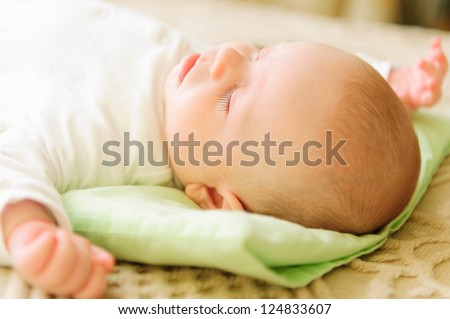 Cute newborn baby sleeping in bed. Shallow depth of field.