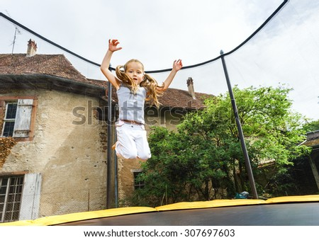 Cute preschooler girl jumping on trampoline, childhood concept