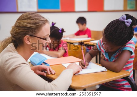 Cute pupil getting help from teacher in classroom at the elementary school