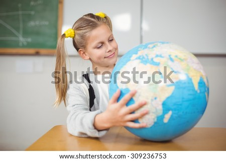 Cute pupil holding globe in a classroom in school
