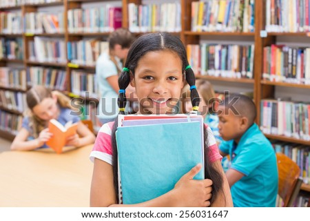 Cute pupil smiling at camera in library at the elementary school
