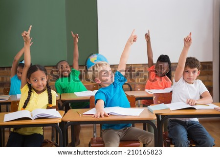 Cute pupils raising their hands at the elementary school
