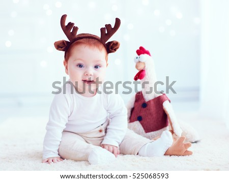 cute redhead baby with rooster toy at home