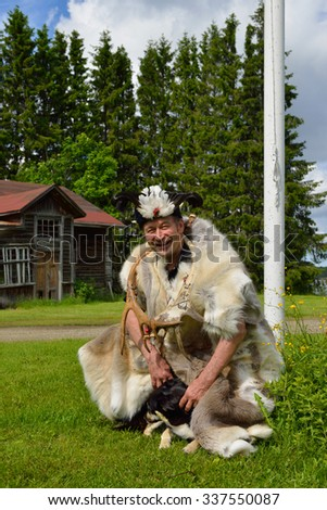 Cute Sami shaman and his assistant - dog. Finnish Lapland