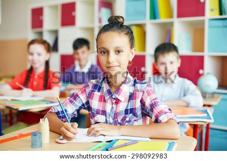 Cute schoolgirl sitting at drawing lesson