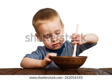 Cute small child boy eats his food from clay bowl with wooden spoon isolated at white