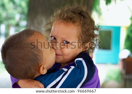 cute small gypsy girl and boy kiss. outdoors