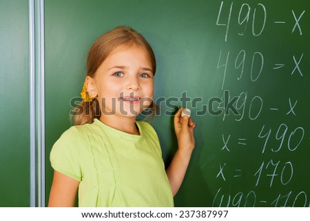 Cute smiling girl with chalk in her hand near  mathematics equation looking straight in front of blackboard during mathematics lesson