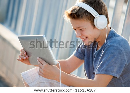 Cute teen boy listening to music with headphones and tablet outside.